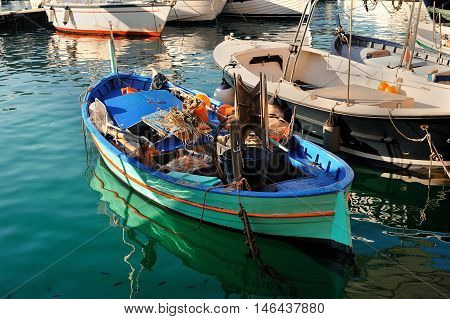 Fishing boat with with reflects in the water with some fishing gear inside