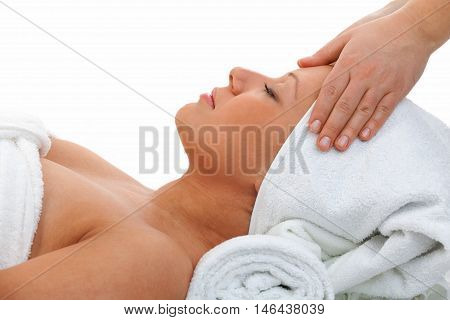 Young woman having a classical massage lying on white bed. Horizontal shot
