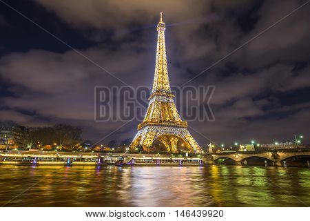 Paris France - February 14 2016: The Eiffel Tower golden lights at night reflected in the Seine River water in Paris France on February 14 2016.