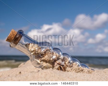 Corked bottle with seashells stuck in the sand on the beach