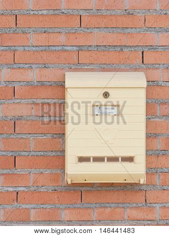 Alicante - October 3 2015: A bright yellow mailbox with the address on the red brick wall of 3 October 2015 Alicante Spain