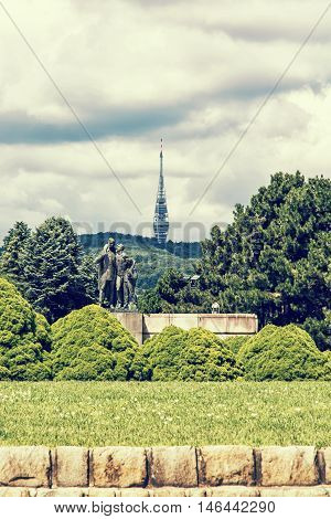 Kamzik tv tower from memorial monument Slavin in Bratislava the capital of Slovak republic. Architectural theme. Travel destination. Yellow photo filter. Symbolic statue greenery and cloudy sky. poster