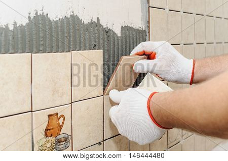 Worker sets tiles on the wall in the kitchen. His hands are placing the tile on the adhesive.