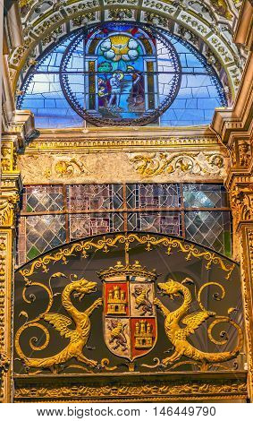 TOLEDO, SPAIN - MAY 16, 2014 Baptism Stained Glass Coat of Arms Cathedral Spanish Flag Toledo Spain. Cathedral started in 1226 finished 1493