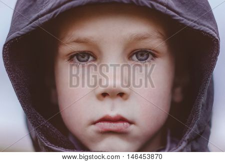 sad boy in a black hood. closeup. kid with big blue eyes and long lashes sadly looking at the camera outdoors