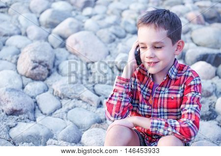 boy enjoys talking on the phone outdoors. child smiling and talking on a cell phone on the beach. the concept of sociability, contact, communications.  empty space for your text.