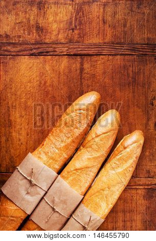 Assortment of baked French baguettes on a wooden background, copy space