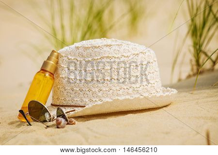 Summer vacations concept. Beach accessories. Straw hat sunglasses and sun oil on sand.
