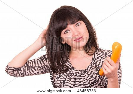 beautiful young puzzled woman using retro orange telephone scratching her head isolated on white