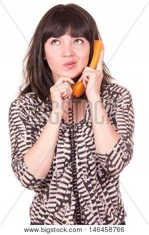 beautiful young disconcerted woman using retro orange telephone waiting isolated on white