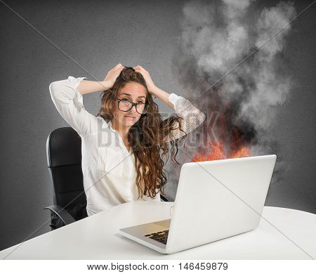 Businesswoman with stressed expression looks at the laptop on fire