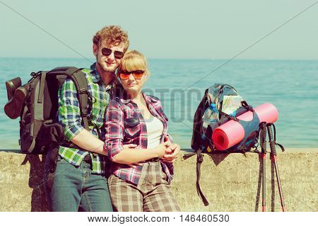 Adventure summer tourism active lifestyle. Young couple backpacker tramping by seaside