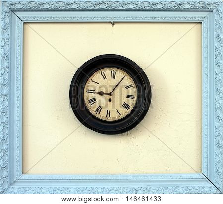 Antique wall clock in a picture frame outdoor