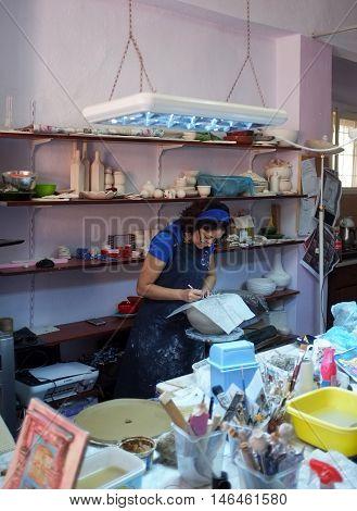 AYVALIK, TURKEY - SEPTEMBER 2ND , 2016: Female ceramic artist works in her studio in Ayvalik, Turkey
