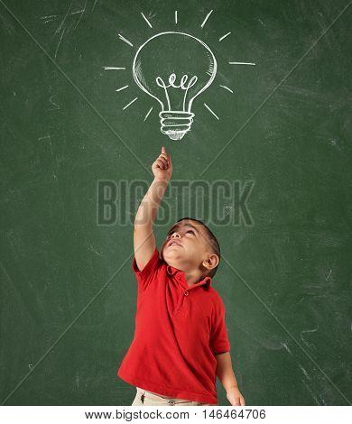 Child points a lightbulb drawn above his head on blackboard