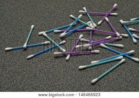 A pile of cotton swabs on a grey background