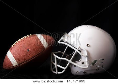 American Football and Helmet shot in the studio, with a black background.