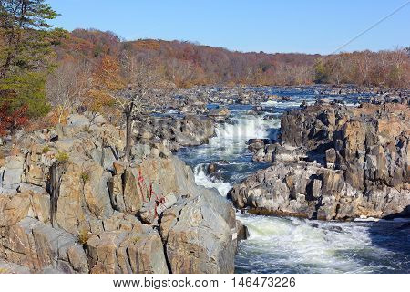 Potomac River in Great Falls state park in autumn Virginia USA. Falls in the river and trees in fall colors.