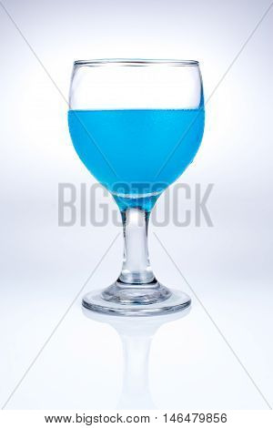 blue beverage in beautiful glass on white background