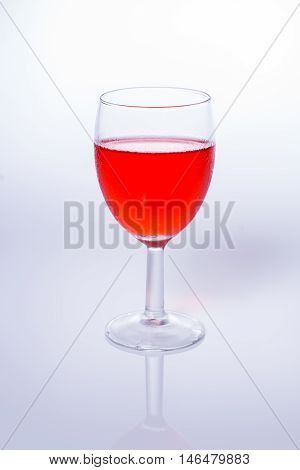 red beverage in beautiful glass on white background