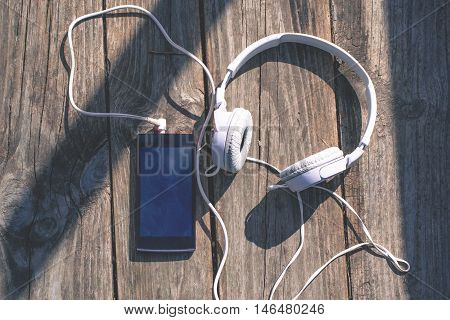 Smart phone and head phone on wooden background