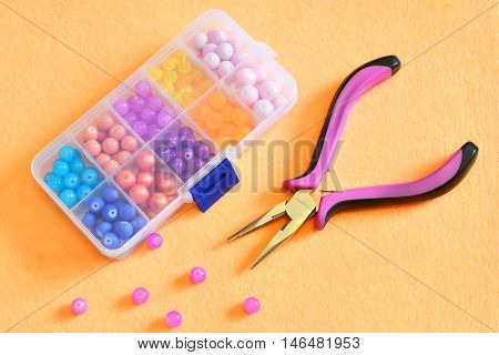 Box of beads, pliers on a beige felt. Craft concept. Craft background