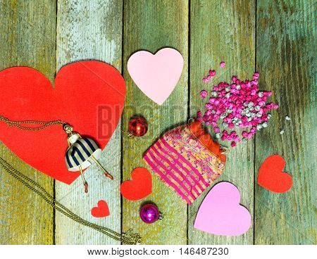 Red paper heart Christmas decoration and a bag with paper lumps to create on the colored background of old wooden planks. The concept of love relationship new year Valentine's day.