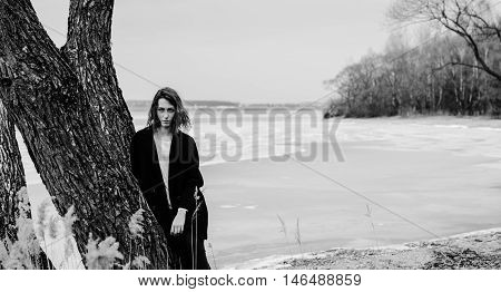 Black and white photo of the pretty girl on the sring beach with tree