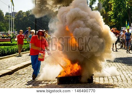 Uzhhorod Ukraine - September 9. 2016: Member of the local section of fire-applied sports liquidate conditional fire during the celebration of the Physical Culture and Sports Day. Similar events are held on this day in all cities of Ukraine.