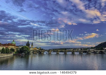 Blue coloured view on the Charles bridge over the Vltava river during sunset with clouds on the sky.