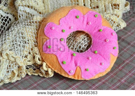 Felt donut. Donut toy sewn from pink and beige felt and embellished with colored beads