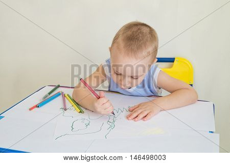Little boy at a desk learning to draws with pencils. Child with a pencil in hand. Photo with copy space and limited depth of field.