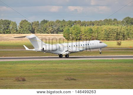 Business jet is touching down the runway with cloudy sky on the background