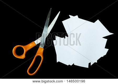 Clear paper cutting and scissors is isolated on black background