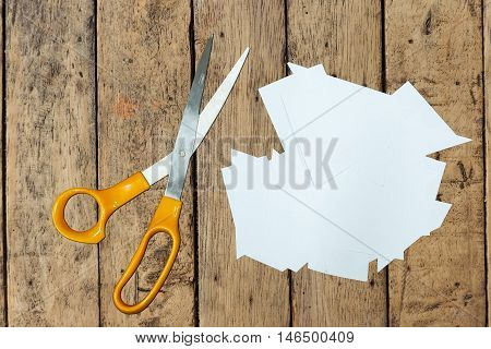 Clear paper cutting and scissors on wood table