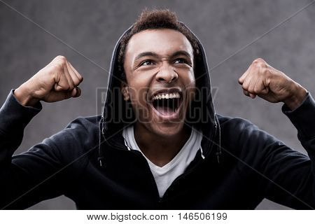 African American man yelling with joy because his sport team has won in national tournament. Concept of coach potato