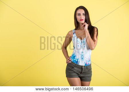 Pensive girl in shorts and tank top standing with her hand near face against yellow background. Concept of thinking about you. Mock up