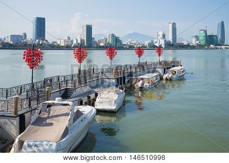 DANANG, VIETNAM - JANUARY 06, 2016: Berth tourist boats on the Han River on a sunny morning. Tourist landmark of the city Danang