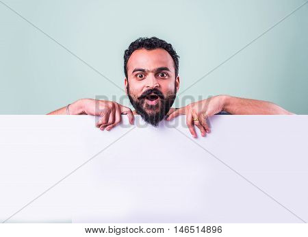 Portrait of handsome indian man with beard holding white blank board. Indian Man holding blank poster.