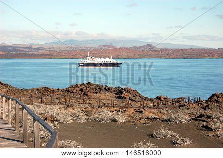 Arid volcanic shore of Sullivan Bay with cruise ship in the distance. Bartolomeo Island, Galapagos.