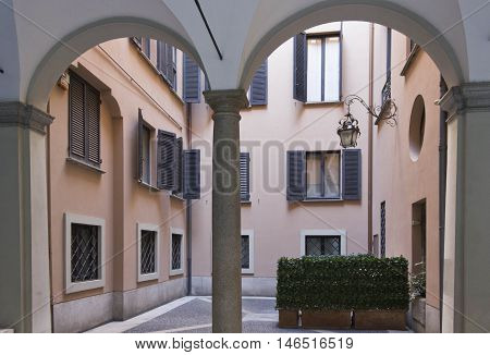MILAN, ITALY - APRIL 13 2015: Residential building in Milan City Centre with historic archway and nobody around