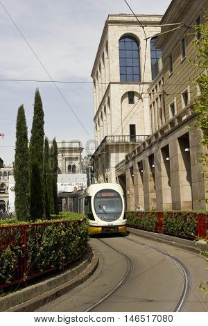 MILAN, ITALY - APRIL 14 2015: Tram number 3 to Gratosoglio in Milan with Museo del Novecento at its side and Piazza del Duomo behind