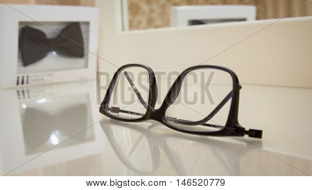 Men's accessories eyeglasses and bow tie near mirror. Shallow dept of field.