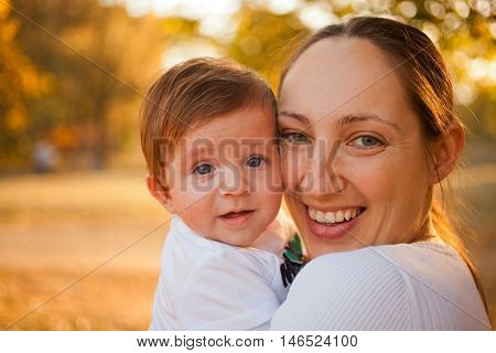 Portrait of mother and baby boy in the park in the autumn