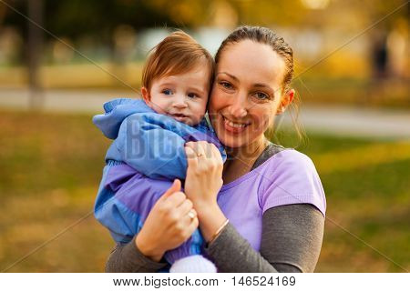 Portrait of mother and baby boy in the park in the autumn. Looking at the camera horizontal shot