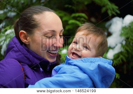 Portrait of mother and baby boy in the park in the winter