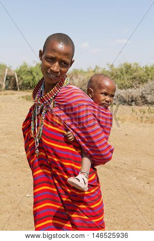 Amboseli Kenya - February 07 2012 - Portrait of masai woman and kid in typical clothing in masai village in Amboseli national park