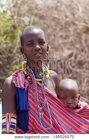 Amboseli Kenya - February 07 2012 - Portrait of masai woman with baby in typical clothing in masai village in Amboseli national park