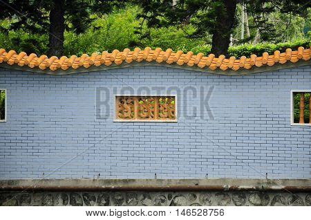 A chinese designed wall with a phoenix or fenghuang in the windows in Guangzhou China near a park in Guangdong province.