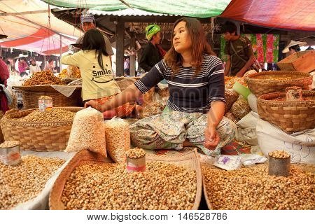 Heho Myanmar - March 02 2011 - Senior Burmese woman selling nuts at the five-day market while sitting on the ground
